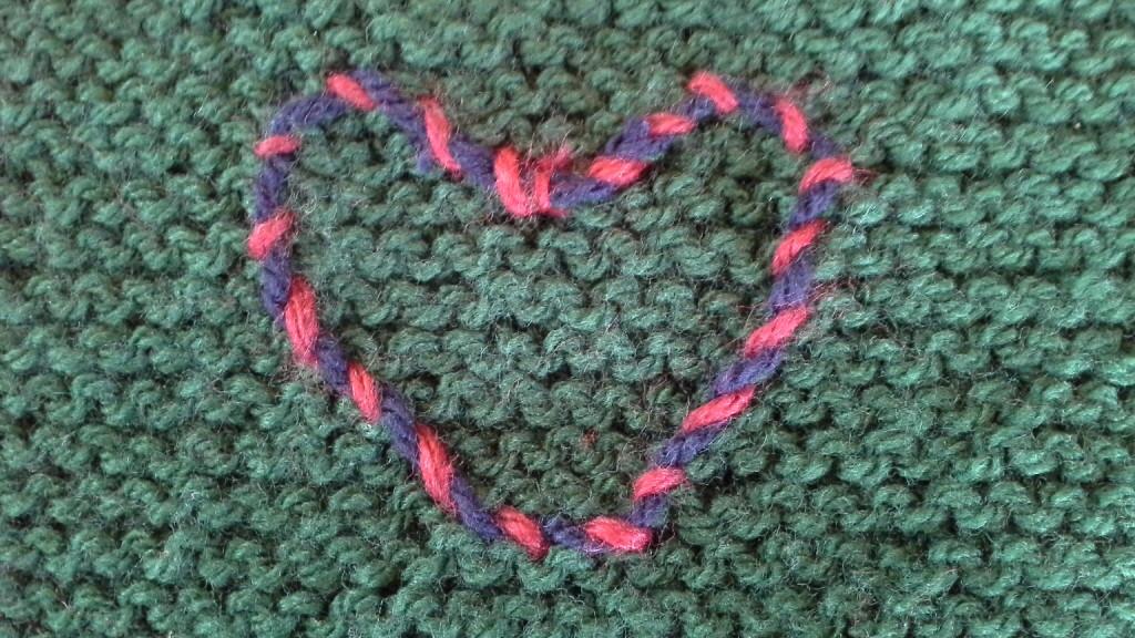 un jeté en tricot et son coeur brodé