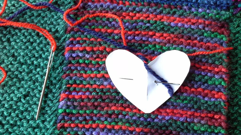 un coeur brodé au jeté tricoté